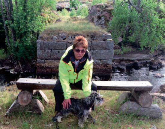 Ing-Marie Gunnarsson med hunden Tissla vid Lönnqvistaställets brofäste över Badebodaån. Foto: Evald Gunnarsso
